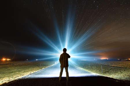 luz natural: Hombre joven que brilla una poderosa antorcha en una noche estrellada en Islandia, en busca de la aurora boreal o extranjeros Foto de archivo
