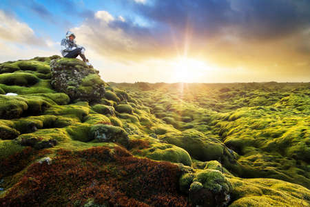 Beautiful tourist posing in the amazing volcanic mossy landscape of Eldhraun at sunrise in Iceland
