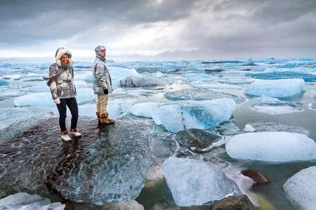 estado del tiempo: Extremadamente hermosas turistas paran en los icebergs enormes en el lago Jokulsarlon en Islandia en invierno