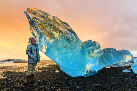 beached: Extremely beautiful young man posing next to a very big chunk of beached ice near Jokulsarlon, Iceland, at sunset