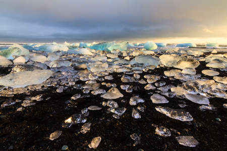 beached: Beautiful beached chunks of ice at the beach at Jokulsarlon, Iceland, at sunset in winter Stock Photo