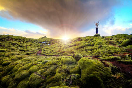 terrain: Beautiful tourist posing in the amazing volcanic mossy landscape of Eldhraun at sunrise in Iceland. HDR
