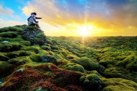 pareja enamorada: Pareja rom�ntica mira la salida del sol sobre el hermoso paisaje volc�nico de Eldhraun en Islandia