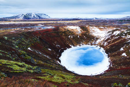 blue circle: Kerid or Kerith volcanic crater lake on the touristic golden circle route in Iceland in winter