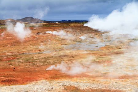 geothermal: Colorful geothermal area Gunnuhver, with steam vents and a geothermal powerplant, in Iceland Stock Photo