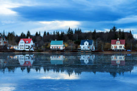 blue hour: Beautiful houses reflected in lake Tjornin in Reykjavik Iceland, during the blue hour in winter Stock Photo