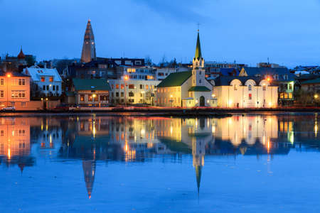 reflection: Beautiful reflection of the cityscape of Reykjavik in lake Tjornin at the blue hour in winter
