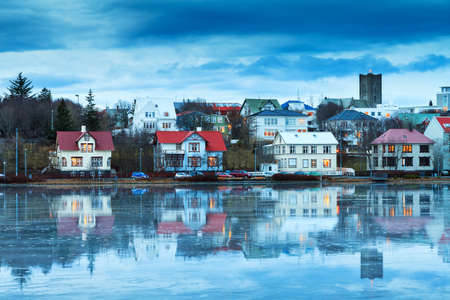 christ church: Beautiful reflection of the cityscape of Reykjavik in lake Tjornin at the blue hour in winter with the Basilica of Christ the King Landakotskirkja