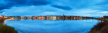 blue hour: Beautiful panorama of the skyline cityscape of Reykjavik, reflected in lake Tjornin at the blue hour in winter Stock Photo