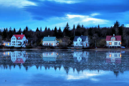 blue hour: Beautiful houses reflected in lake Tjornin in Reykjavik Iceland, during the blue hour in winter, HDR Stock Photo