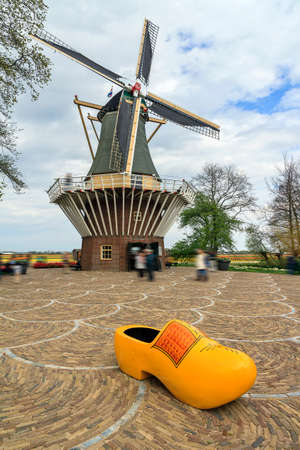 klompen: Typical dutch image of a large wooden clog klomp in front of a windmill