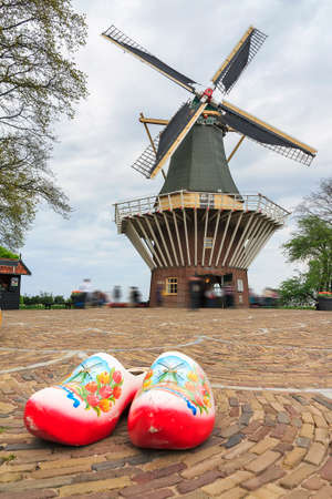 klompen: Typical dutch image of large wooden clogs klompen in front of a windmill Stock Photo