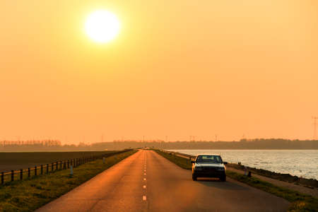 dyke: Mysterious car on the levee at sunset in the Netherlands
