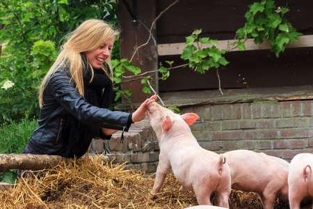animales de granja: Joven chica muy rubia que se divierte con los lechones en el zool�gico de mascotas en primavera