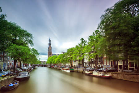 prinsengracht: Beautiful long exposure of the Westerkerk church at the UNESCO world heritage Prinsengracht canal in Amsterdam