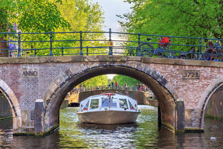 lord's: Canal cruise boat goes under the bridge over the canal in Leiden at the Patricians or Lords canal Herengracht in Amsterdam in spring