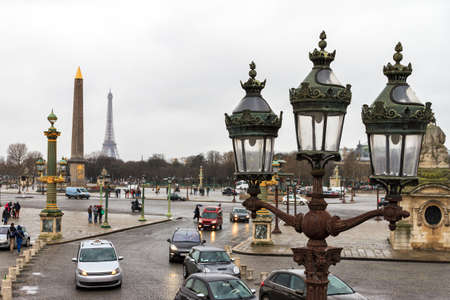 concorde: Rainy day at place de la Concorde in Paris, France. Obelisk and Eiffel tower in the background, lantern in the front Stock Photo