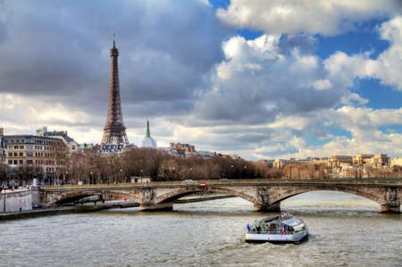 tourist attraction: Tourist boat at the Seine in Paris with the Eiffel tower in the background on a cloudy winter day Stock Photo