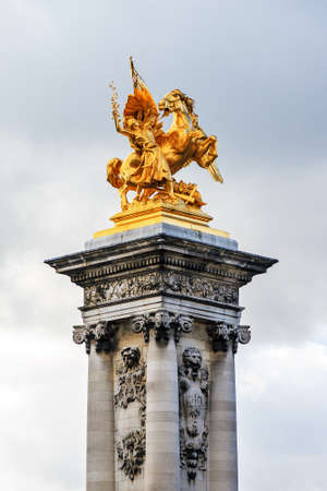 alexandre: Golden statue on a pillar at the Pont Alexandre III at a cloudy winter day in Paris