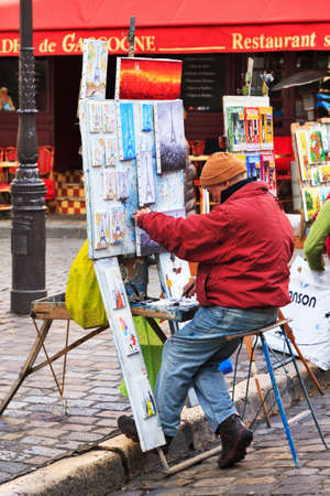 parisian scene: Artist working on a painting at the Place du Tertre in Paris, France, on February 21, 2014