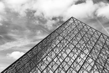 louvre pyramid: Beautiful view of the Louvre pyramid in Paris on a cloudy winter day in BW