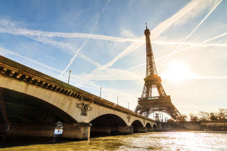 tourist attraction: Beautiful backlit Eiffel tower at the Seine river with a dramatic sky in winter