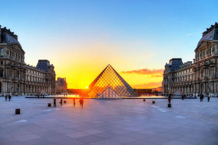 museum visit: Tourists in spring visit the Louvre museum at sunset in Paris, France, on April 14, 2014