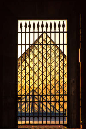 louvre pyramid: Louvre pyramid seen through a gate of the museum at sunset in Paris, France, on April 14, 2014 Editorial
