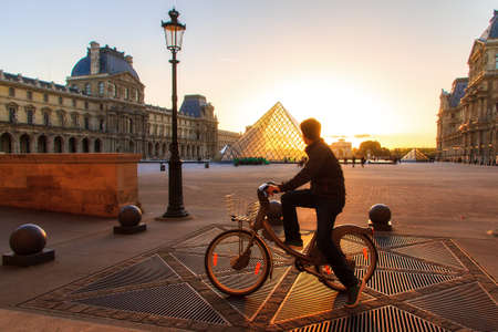 louvre pyramid: A tourist looks at the Louvre pyramid at sunset from a rented bicycle in Paris, France, on April 14, 2014