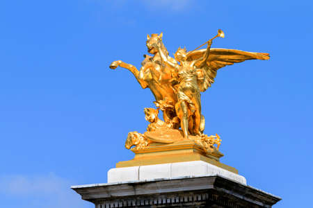 alexandre: Golden statue against a blue sky on top of the pont Alexandre III at Invalides in Paris, France