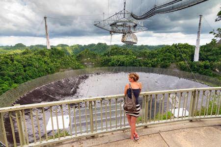 radio telescope: Beautiful woman looks at the Arecibo Observatory radio telescope in the hills of Arecibo, Puerto Rico Editorial