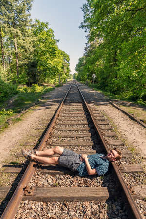 Conceptual image of a young man taking a break (from life) and lays down on the rails of a train track Stock Photo
