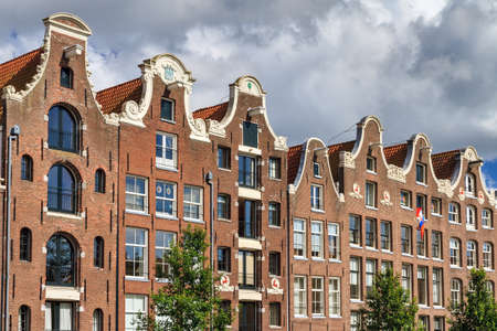 Beautiful view of the canal houses at the Prinsengracht canal  in Amsterdam, the Netherlands, on a summer day with clouds