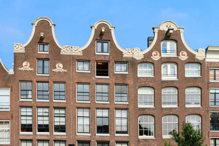 Beautiful view of the canal houses at the Prinsengracht canal  in Amsterdam, the Netherlands, on a summer day with blue sky
