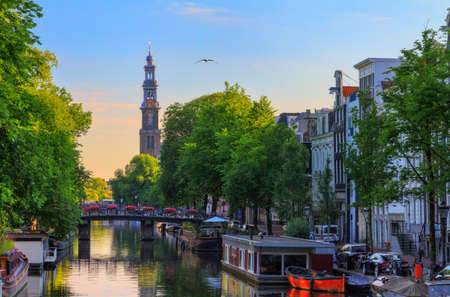 UNESCO world heritage Prinsengracht canal with the Westerkerk (Western church) on a summer morning with a blue sky in Amsterdam, The Netherlands Stock Photo