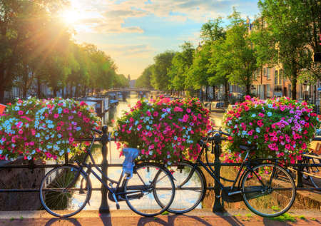 Beautiful summer sunrise on the famous canals of Amsterdam, The Netherlands, with vibrant flowers and bicycles on a bridge Stock Photo