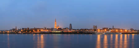 Beautiful cityscape panorama of the skyline of Antwerp, Belgium, during the blue hour seen from the shore of the river Scheldt Stock Photo