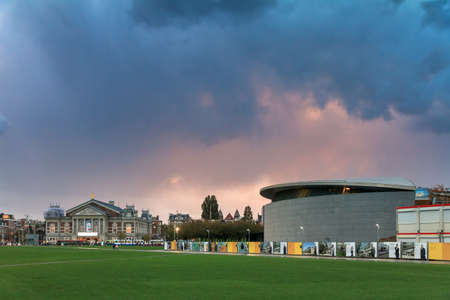 Ominous thunderclouds at sunset over the Museum Square (Museumplein) in Amsterdam, the Netherlands, looking towards the Royal Concert building (Koninklijk Concertgebouw) and the Van Gogh museum