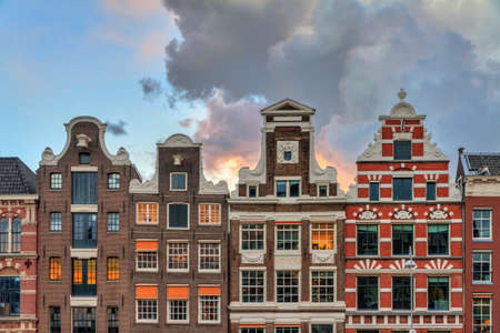 Facades of typical dutch manor houses  heritage canals of Amsterdam, The Netherlands, with a summer sunset sky