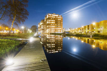 Modern new residential district in Leiden, The Netherlands, with apartment buildings reflected in the water at night, seen from a jetty