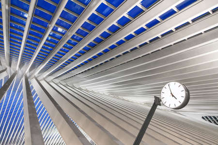 Beautiful abstract view of the interior of the modern architecture railway station Liege-Guillemins with steel shapes and lines and a clock in the blue hour in Belgium Editorial