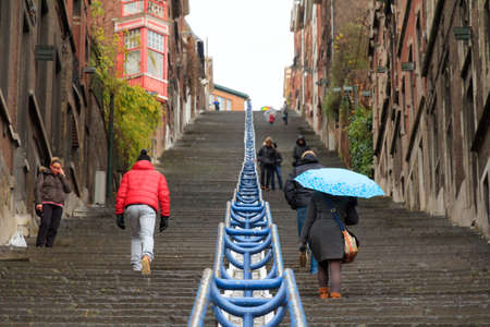 Tourists and local people climbing up the Montagne de Bueren staircase in Liege, Belgium, on a rainy December afternoon in 2014 Stock Photo