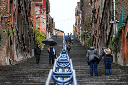 Tourists and local people climbing up the Montagne de Bueren staircase in Liege, Belgium, on a rainy December afternoon in 2014 Editorial