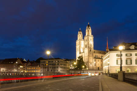 Beautiful cityscape of Zurich, Switzerland, with the Grossmünster Protestant church, seen from the shore of the river Limmat at night in summer