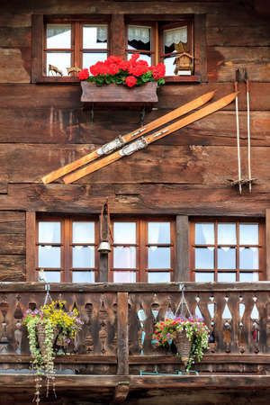 Beautiful traditional wooden house in the streets of the alpine village Grimentz, Switzerland, in the canton Valais, municipality Anniviers, with geranium flowers and ancient ski's on the facade