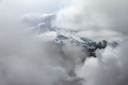 Beautiful aerial view of mountain peaks with snow in the swiss alps with clouds