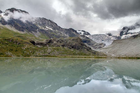 Beautiful landscape view of the Moiry glacier reflected in a milky blue lake of melted ice with a ominous sky with clouds in summer in the Swiss pennine alps near Grimentz, Valais, Switzerland