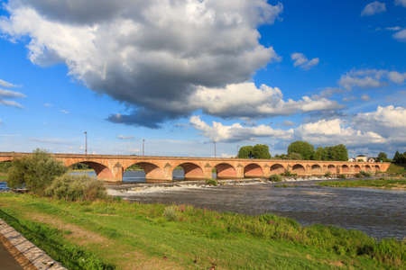Beautiful summer view of the arched bridge over the river Loire (Pont de Loire) in Nevers, France, with a blue sky with clouds Stock Photo