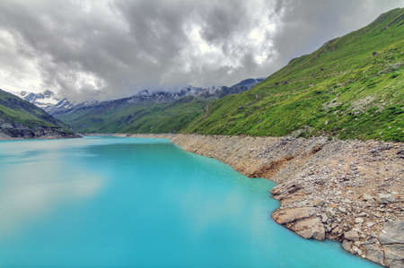 Beautiful view of reservoir lake Moiry (lac de Moiry) with vibrant turquoise blue water at a low level in summer in Valais, Switzerland 스톡 콘텐츠