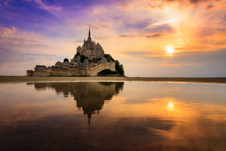 Beautiful view of historic landmark Le Mont Saint-Michel in Normandy, France, a famous UNESCO world heritage site and tourist attraction, at sunset with reflection Imagens